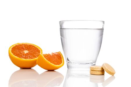 Glass of water with oranges and vitamin c effervescent tablet on white background