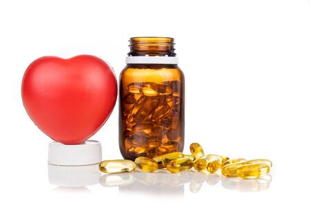 Fish oil gel capsule with bottle and heart shaped prop against white background. It containing omega-3 polyunsaturated acid EPA and DHA enhances heart and health.