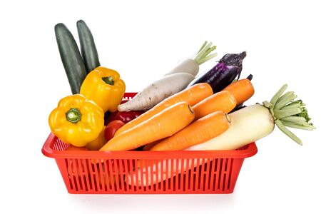 Basket of fresh assorted vegetables carrots, radish, capsicum, tomato, cucumber, brinjal on white background