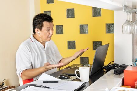 Matured Asian business man raises both hands in stressful expression in work from home video conference call