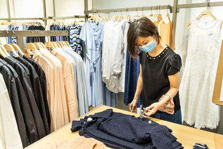 Asian woman shopping apparels in clothing boutique with protective face mask as new normal requirement in Malaysia