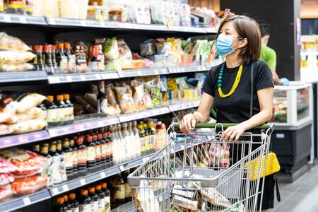 Asian woman shopping groceries in supermarket with protective face mask as new normal requirement in Malaysia