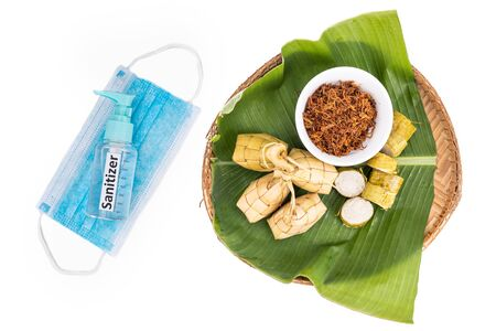 Ketupat, rice dumpling, lemang, serunding with sanitizer and face mask. Restricted celebration during covid-19 pandemic in Malaysia
