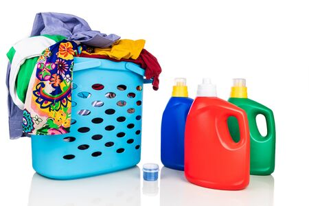 Regular liquid laundry detergent of various fragrance variant with basket full of clothes against white background