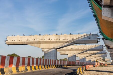 Construction of highway overpass bridge and rail transit infrastructure in progress with morning sun rays in Malaysia Banco de Imagens