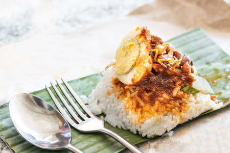 Simple serving of authentic nasi lemak bungkus wrapped with banana leaf Stock Photo