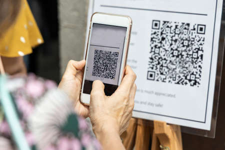 Modified inactive QR Code used. Person scanning QR code with smartphone to register details before enter outlet to comply with contact tracing rule to manage covid-19 spread.
