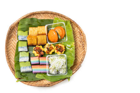 Overhead view of traditional nyonya kueh on banana leaf rattan tray on white background Stock Photo