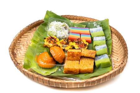 Traditional nyonya kueh on banana leaf rattan tray on white background
