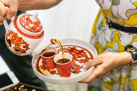 Person filling two disposable cups with tea in Chinese wedding ceremony. Chinese word on tray, pot and cup is translated as Celebration in English.
