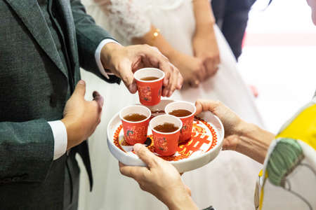 Closeup of bridegroom holding tea to serve elderly during Chinese wedding tea ceremony. Chinese word on tray and cup is translated as Celebration in English.