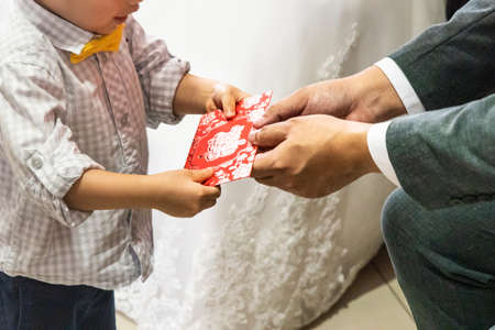 Closeup of Bride and Groom receiving red envelope from elderly during Chinese wedding tea ceremony. Chinese word envelope is translated as Celebration in English.