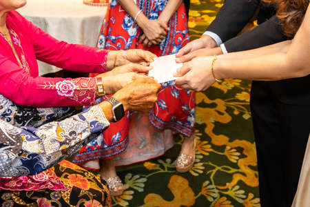 Closeup of Bride and Groom receiving red envelope from elderly during Chinese wedding tea ceremony
