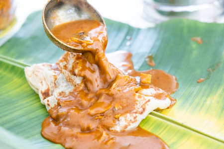 Curry being poured onto roti canai or paratha served on banana leaf