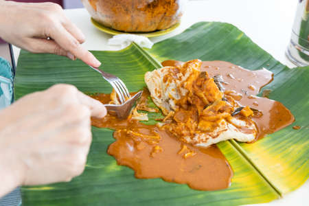 Person eating roti canai or paratha served with curry served on banana leaf 版權商用圖片