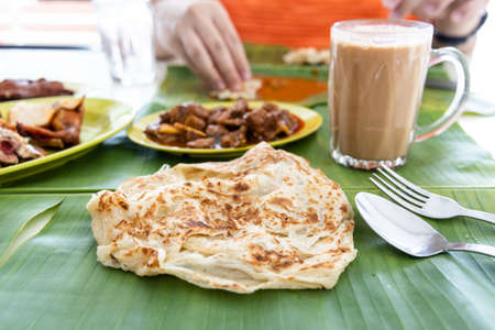 Roti canai or paratha served on banana leaf, with mutton curry and fried chicken, and popular teh tarik