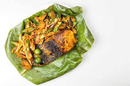 Overhead view of popular grilled stingray fish with spices and vegetable served on banana leaf Banque d'images
