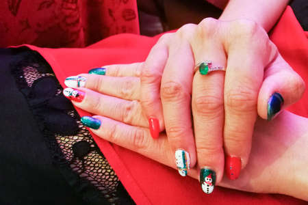 Manicured acrylic nails with beautiful multi colored nail art on red background.