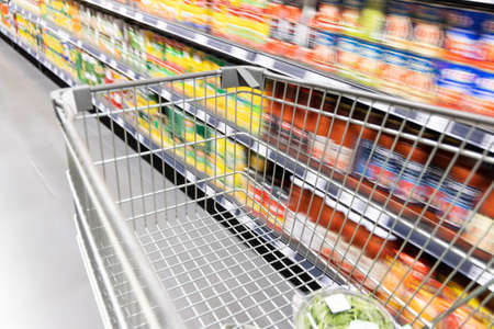 Shopping trolley cart moving in supermarket with motion blur aisle background