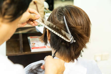 Close-up of hair dresser barber cutting hair of female client with scissors and comb