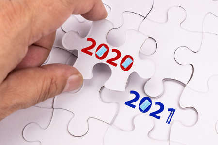 Concept of finger flipping puzzle transiting from 2020 to 2021 new year with mask and vaccine syringe