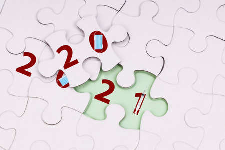 Concept of flipped puzzle transiting from 2020 to 2021 new year with mask and vaccine syringe