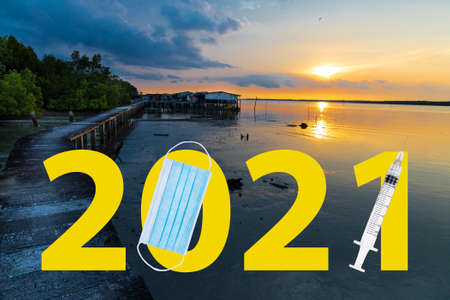 Welcome 2021 text against sunrise at seaside with face mask and syringe suggesting Covid-19 vaccination year