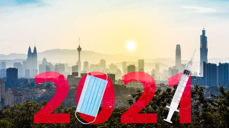 Welcome 2021 text against Kuala Lumpur cityscape with face mask and syringe suggesting Covid-19 vaccination year