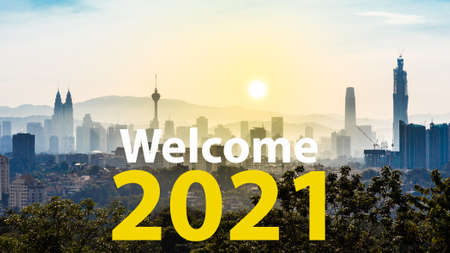 Welcome 2021 text against Kuala Lumpur cityscape as background during sunrise
