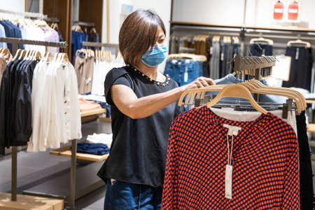 Asian woman shopping apparels in clothing boutique with protective face mask