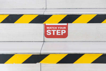 Watch Your Step word signage with yellow black strip on stair steps 写真素材