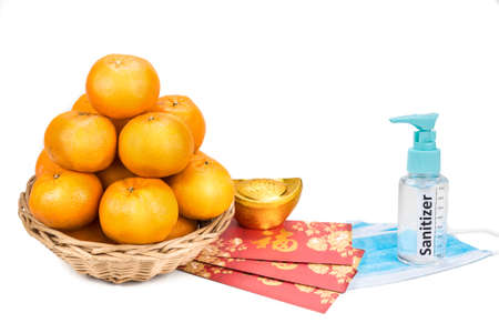 Chinese new year new greetings wtih tangerine oranges, red envelop and face mask sanitizer for protection. Chinese word translated as Prosperity in English.