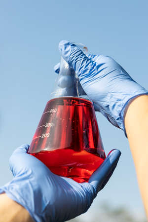Hand with gloves holding beaker with red color unrefined palm oil against blue sky