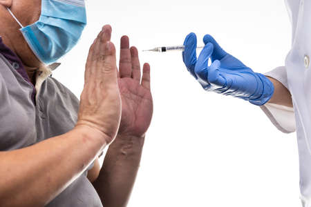 Fearful worried middle age man reacting to medical practitioner holding syringe loaded with Covid-19 vaccine