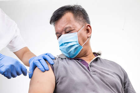 Close-up of Asian middle age man receiving  vaccine injection onto the arm