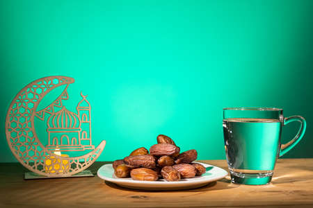 Muslim iftar of breaking of fast during Ramadan month with preserved sweet dates and water. Decorative crescent and mosque as prop