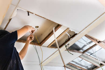 Electrician concealing electicity power wire lines within plastic tube embeded into ceiling.