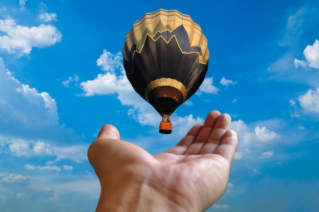 Hand Holding hot air balloon Stock Photo