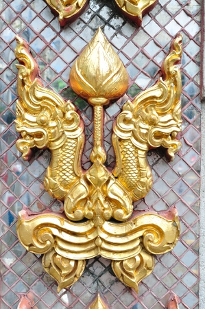 Golden naga head on decorated mirror pattern.   It is decoration on Thai temple wall. photo