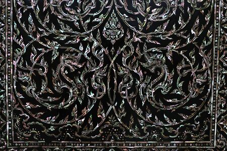 inlay: Traditional Thai art on black wood carving door decorated with Mother of pearl inlay.