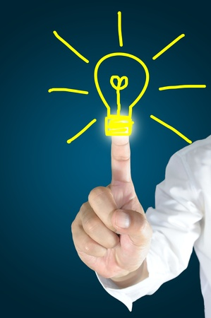 safe investment: Male hand touch or draw light bulb on touch screen