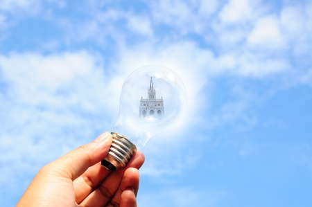 electric green: light bulb with christ church in male hand