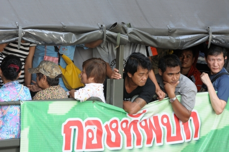 BANGKOK - NOVEMBER 1  Unidentified people take a military truck to go to office and residence, instead of bus or taxi, at the Charunsanitwong rd  near Bangplad junction on November 1, 2011 in Bangkok, Thailand  The area is located on the west side of the  Stock Photo - 20473541