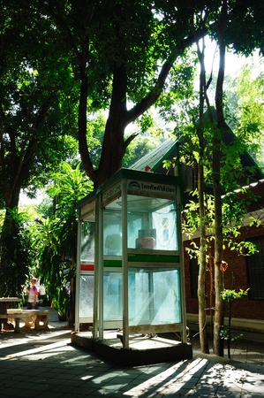 teclado numerico: Cabina telefónica brillante bajo la sombra de madera grande en Wat Umong templo, Chiang Mai, Tailandia