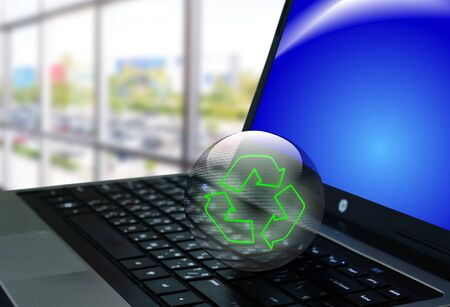 Crystal ball of recycle symbol on notebook or laptop computer photo