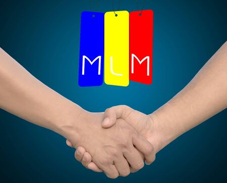 mlm: Hand shake or hand in hand with the word MLM on iron tag