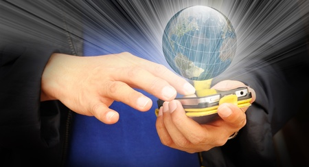 Hand of business man touch screen of mobile phone with ray of light shining through earth globe photo