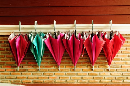 Pattern of umbrella hang on cement and wood wall photo