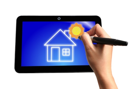 Hand of Business Man Draw House and Sun on Touch screen of Tablet PC photo
