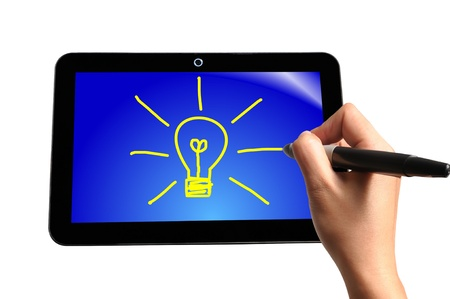 Hand of Business Man Draw Light Bulb on Touch screen of Tablet PC photo
